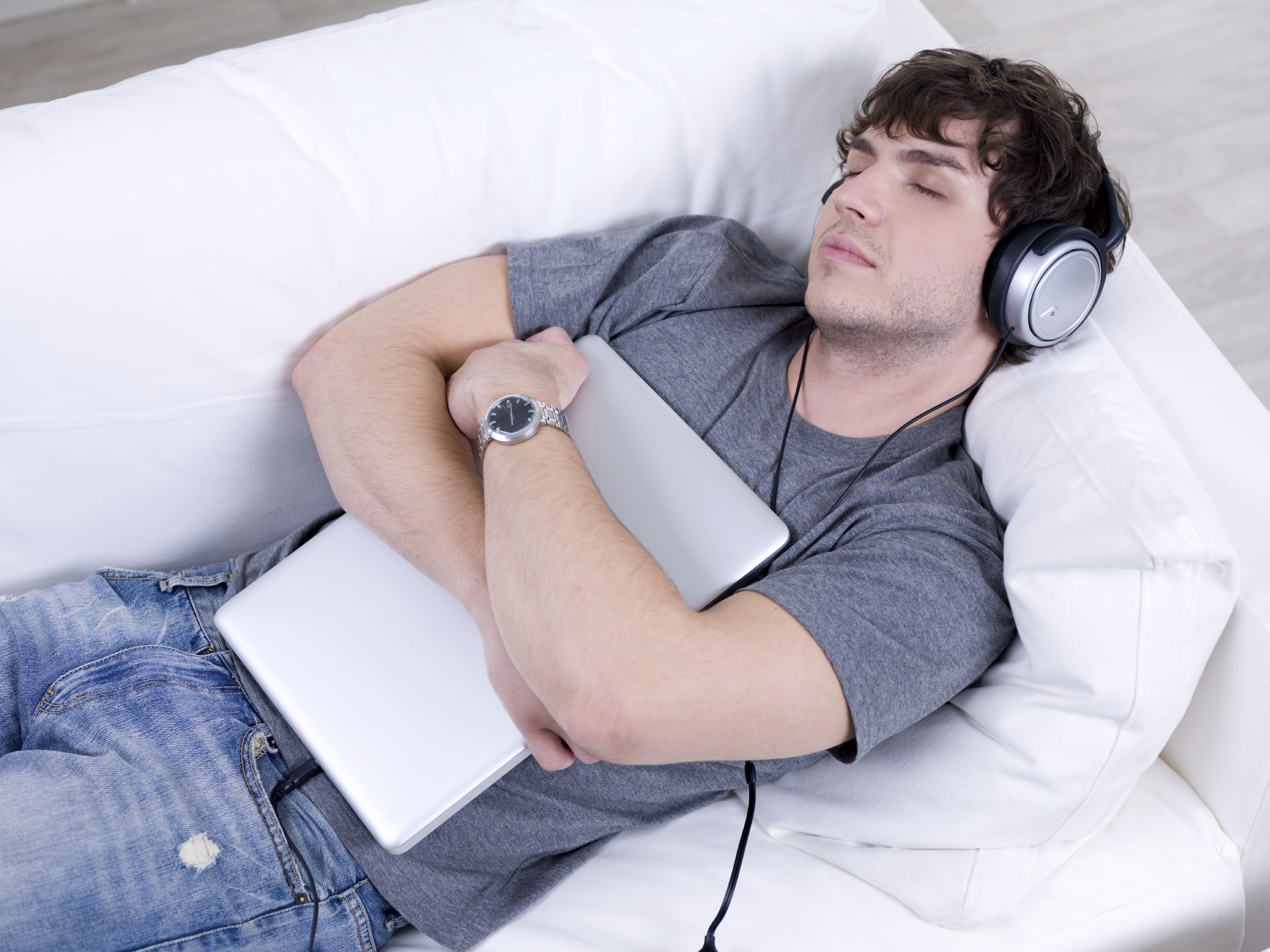Man listening music in headphone and sleeping in embrace with laptop on the sofa